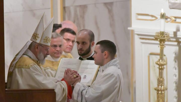 Diaconate candidate making promise to bishop
